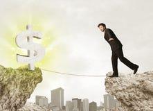 Homme d'affaires sur la montagne de roche avec une marque du dollar Photo stock