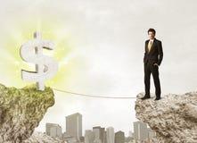 Homme d'affaires sur la montagne de roche avec une marque du dollar Photo libre de droits