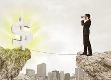 Homme d'affaires sur la montagne de roche avec une marque du dollar Photographie stock