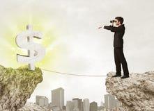 Homme d'affaires sur la montagne de roche avec une marque du dollar Photographie stock libre de droits