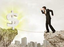 Homme d'affaires sur la montagne de roche avec une marque du dollar Image stock