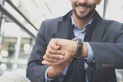 Homme d'affaires sur la rue de ville vérifiant le temps sur la montre Fin vers le haut photos libres de droits