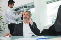 Homme d'affaires sur le collègue de téléphone à l'arrière-plan Photo stock