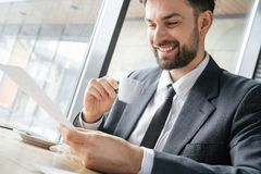 Homme d'affaires sur le déjeuner d'affaires au document potable se reposant de lecture d'expresso de restaurant gai photo libre de droits