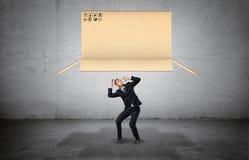 Homme d'affaires sur le fond concret se recroquevillant au-dessous d'une grande boîte ouverte de carton tombant sur lui Image libre de droits