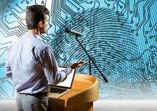 Homme d'affaires sur le podium parlant à la conférence avec le fond de la science et technologie d'empreinte digitale Images libres de droits