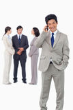 Homme d'affaires sur le téléphone portable avec l'équipe derrière lui Photo libre de droits