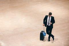 Homme d'affaires sur le terminal d'aéroport avec la valise et le téléphone portable Images libres de droits