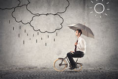 Homme d'affaires sur le vélo tenant un parapluie Image libre de droits