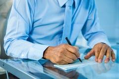 Homme d'affaires sur son document de signature de bureau Images stock