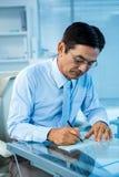 Homme d'affaires sur son document de signature de bureau Photos stock