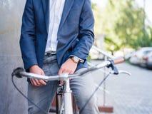 Homme d'affaires sur un plan rapproché de bicyclette avec une horloge chère Photo stock