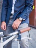Homme d'affaires sur un plan rapproché de bicyclette avec une horloge chère Photo libre de droits