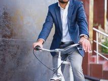 Homme d'affaires sur un plan rapproché de bicyclette avec une horloge chère Image stock
