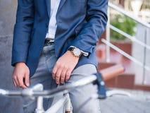 Homme d'affaires sur un plan rapproché de bicyclette avec une horloge chère Photos stock