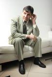 Homme d'affaires sur un sofa de cuir blanc Images libres de droits