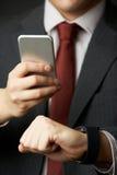 Homme d'affaires Synchronizing Smart Watch avec le téléphone portable Photos libres de droits