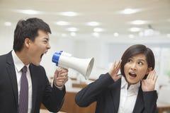 Homme d'affaires Talking dans le mégaphone par l'oreille de la femme d'affaires images stock