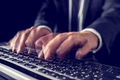 Homme d'affaires tapant sur un clavier d'ordinateur Photographie stock libre de droits