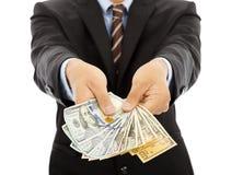 Homme d'affaires tenant argent liquide de dollar US D'isolement sur le blanc Photos stock