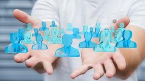Homme d'affaires tenant 3D rendant le groupe de personnes bleues Images stock