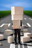 Homme d'affaires tenant des boîtes de carton sur la route avec beaucoup de boxe Photographie stock libre de droits