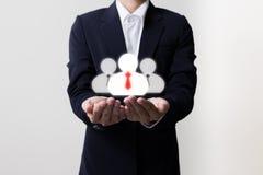 Homme d'affaires tenant des directeurs et des symboles d'équipe image stock