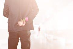 Homme d'affaires tenant des roses derrière le sien de retour avec les femmes brouillées sur le chemin de chemin (le vintage mou d Photos stock