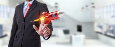 Homme d'affaires tenant et touchant un rendu de la fusée 3D Photographie stock
