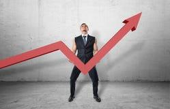 Homme d'affaires tenant grand graphe linéaire rouge avec une flèche retournée et essayant de la soulever  Image stock