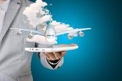 Homme d'affaires tenant l'avion actuel de comprimé dans sa main Images libres de droits
