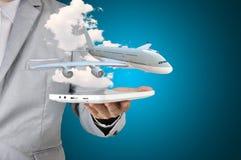 Homme d'affaires tenant l'avion actuel de comprimé dans sa main Photos stock