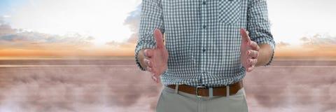 Homme d'affaires tenant l'espace aérien invisible devant des nuages Image stock