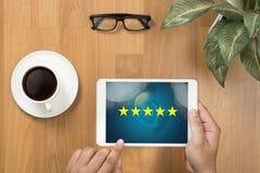 Homme d'affaires tenant l'estimation de cinq étoiles, examen, estimation d'augmentation ou image stock