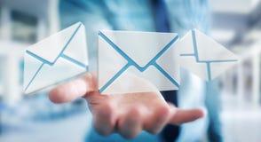 Homme d'affaires tenant l'icône d'email de vol du rendu 3D dans sa main Photo stock