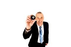 Homme d'affaires tenant la boule de billard noire Image stock