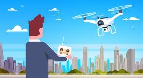Homme d'affaires tenant la mouche à distance de For Modern Drone de contrôleur au-dessus des bâtiments de ville Image stock