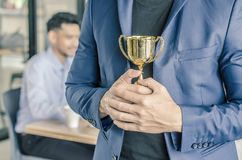 Homme d'affaires tenant la récompense de trophée pour le succès dans les affaires, Images stock