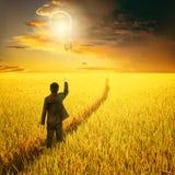 Homme d'affaires tenant le ballon d'ampoule sur le chemin dans le domaine de riz et le coucher du soleil jaunes de nuage de pluie Photographie stock
