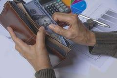 Homme d'affaires tenant le billet de banque dans le portefeuille dans sa main pour financier image stock