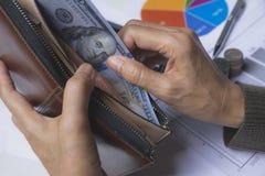 Homme d'affaires tenant le billet de banque dans le portefeuille dans sa main pour financier images stock