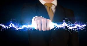 Homme d'affaires tenant le boulon léger de l'électricité dans des ses mains Image libre de droits