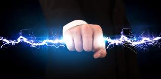 Homme d'affaires tenant le boulon léger de l'électricité dans des ses mains Photographie stock
