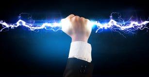 Homme d'affaires tenant le boulon léger de l'électricité dans des ses mains Photographie stock libre de droits