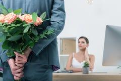 Homme d'affaires tenant le bouquet des roses pour son collègue s'asseyant sur le lieu de travail Photographie stock libre de droits