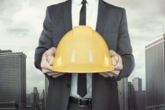 Homme d'affaires tenant le casque jaune dans des mains dessus Photographie stock libre de droits