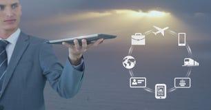 Homme d'affaires tenant le comprimé avec des icônes d'affaires contre le ciel gris mou avec le soleil Image stock