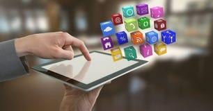 Homme d'affaires tenant le comprimé avec des icônes d'apps dans le bureau images stock