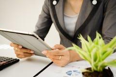 Homme d'affaires tenant le comprimé numérique au bureau sur la table avec des données de graphique de document Image stock