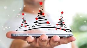 Homme d'affaires tenant le croquis d'arbres de Noël au-dessus du téléphone portable Images libres de droits